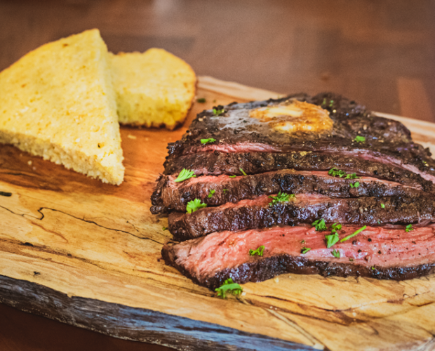 Photograph of sliced grilled Canadian Wagyu beef bavette on a wooden cutting board